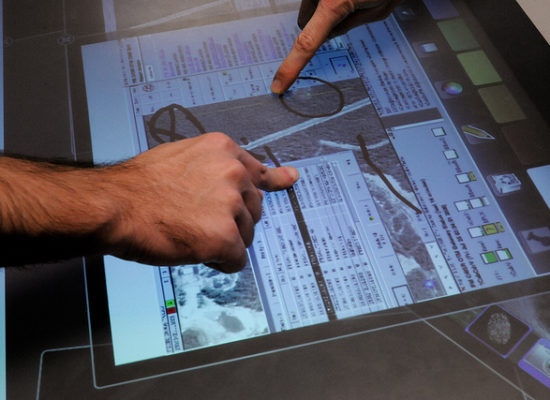 Two sets of fingers trying out some new hardware and software on a touchscreen representing the testing by users.